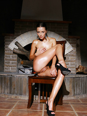 Anna AJ's towering physique, with oiled skin, her long black hair tied back to reveal her erotic expressions as she poses sensually, cup[ping her breasts and caressing her sensitive assets